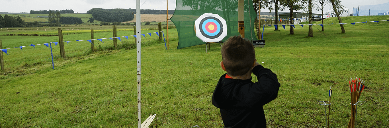 Boy on a school trip about to shoot arrow at target during archery on an away day in Edinburgh