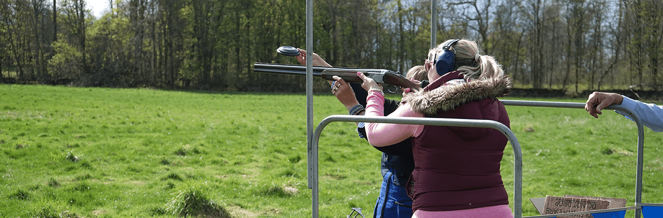 Woman with Instrutor being taught how to clay pigeon shoot at a Hen Party in Edinburgh