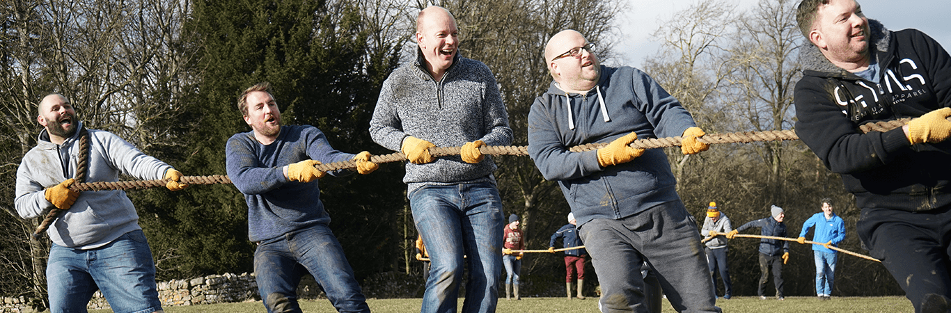 Four men all members of the same team doing a tug of war during a Mini Highland Games in Edinburgh at Great Away Days